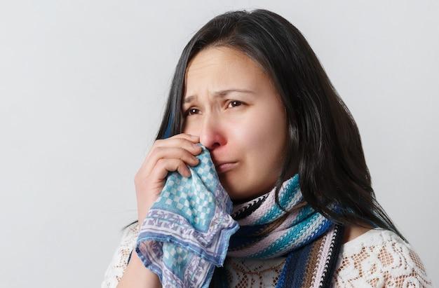 Donna triste con naso che cola usa il fazzoletto