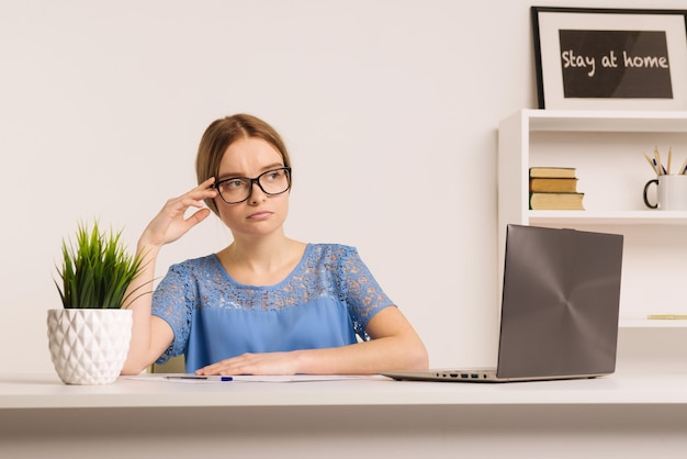 Imprenditore triste e preoccupato che lavora in linea con un laptop in una scrivania in ufficio oa casa