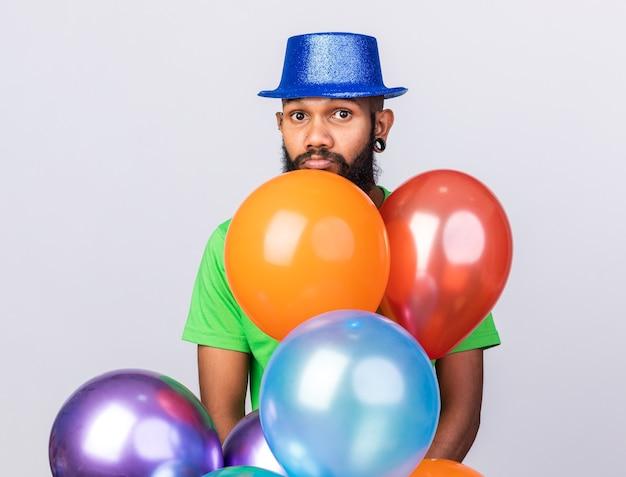 Triste giovane ragazzo afroamericano che indossa un cappello da festa in piedi dietro palloncini isolati sul muro bianco