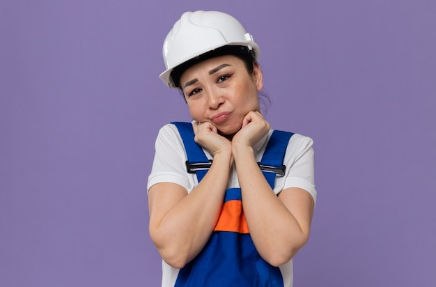 Triste giovane donna asiatica del costruttore con il casco di sicurezza bianco che si mette le mani sul viso e guarda