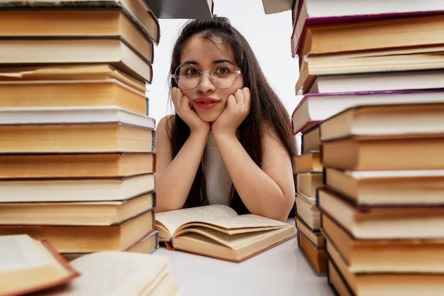 Triste giovane ragazza bruna con gli occhiali con i capelli lunghi si siede a un tavolo con una pila di libri. istruzione e formazione. isolato su uno sfondo bianco. avvicinamento.