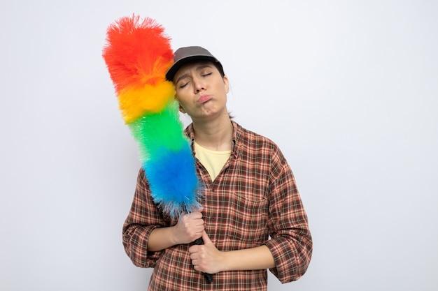 Triste giovane donna delle pulizie in abiti casual e berretto con in mano una spazzola colorata per spolverini che sembra stanca e annoiata che si increspa le labbra in piedi sul bianco