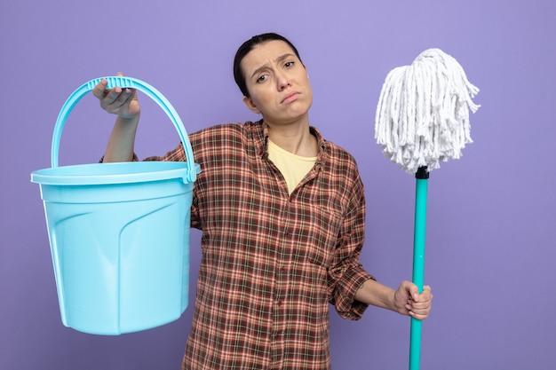 Triste giovane donna delle pulizie in abiti casual che tiene mop e secchio stanca ed esausta in piedi sul viola