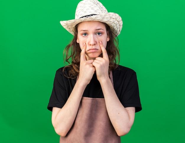Triste giovane giardiniere femminile che indossa un cappello da giardinaggio che tira giù le palpebre isolate sulla parete verde