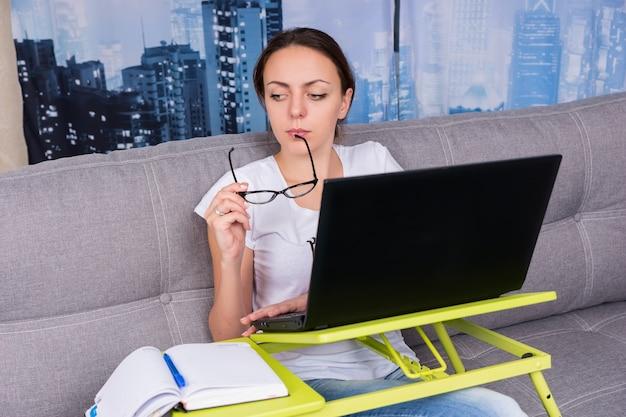 La ragazza triste ha messo gli occhiali alla bocca mentre lavorava su un laptop facendo i suoi affari da casa seduta su un divano nel soggiorno in un'atmosfera rilassata