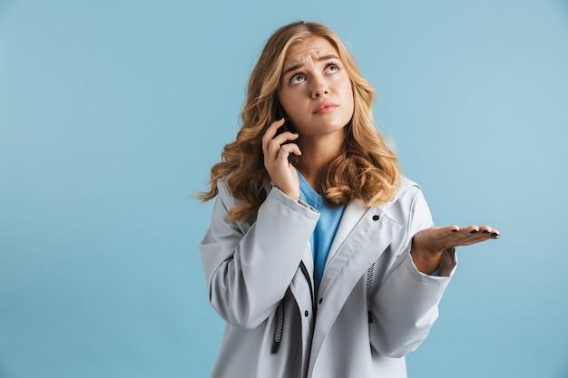 Triste ragazza che indossa un impermeabile in piedi con la mano outsretched isolata, parlando al telefono cellulare