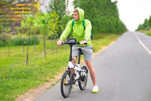 Triste giovane ragazzo in sella a una bicicletta elettrica in uno sport di stile di vita attivo di un ragazzo del parco estivo