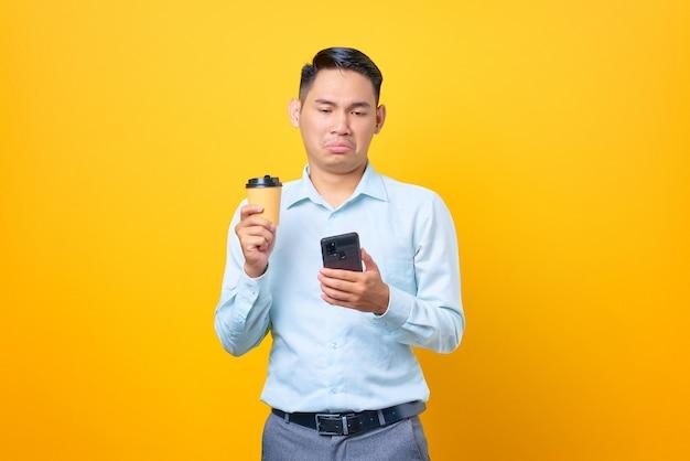 Triste giovane uomo d'affari bello che tiene smartphone e tazza di caffè su sfondo giallo
