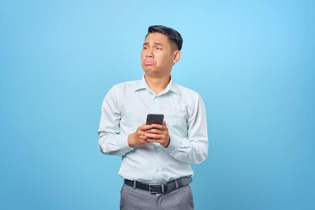 Triste giovane uomo d'affari bello che tiene smartphone e guarda da parte su sfondo blu