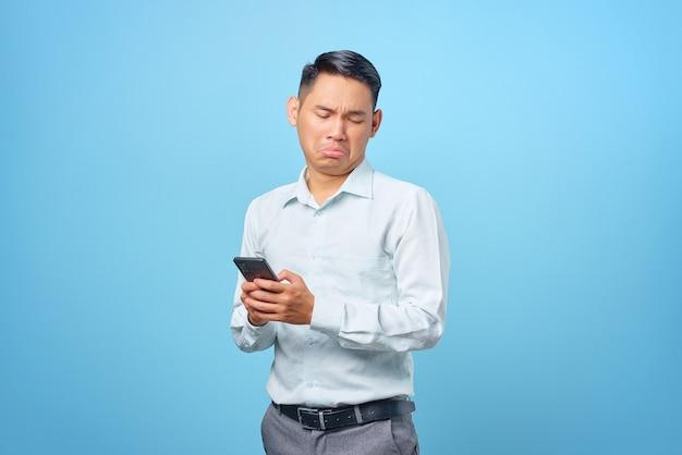 Triste giovane uomo d'affari bello che tiene e usa smartphone su sfondo blu