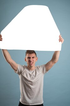 Giovane triste che tiene banner pubblicitario bianco giovane triste con banner pubblicitario vuoto.