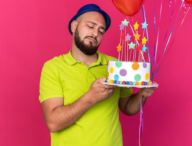 Giovane triste che indossa un cappello da festa blu che tiene palloncini e guarda la torta in mano