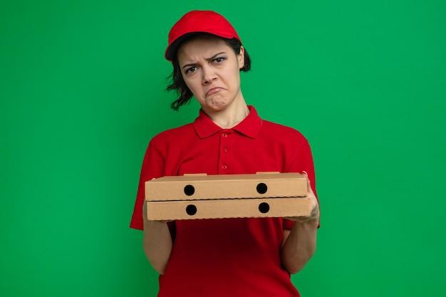 Triste giovane graziosa donna delle consegne che tiene in mano scatole per pizza