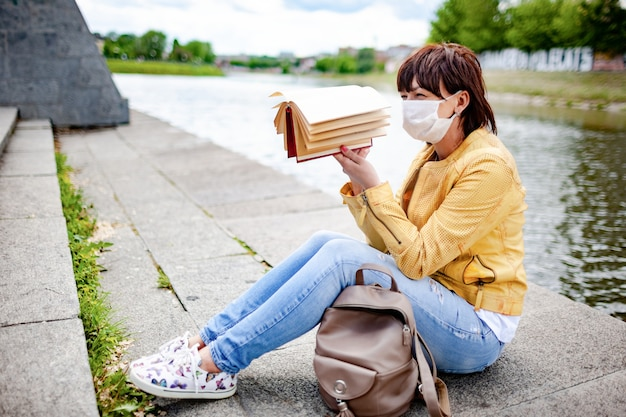 Triste giovane donna in abiti casual e maschera protettiva tiene stancamente il libro