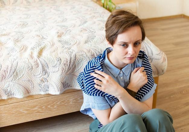 Una giovane donna triste incrociò le braccia sul petto. si siede per terra nella sua camera da letto a casa