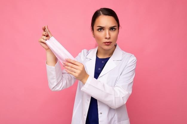 La giovane donna triste tiene e indossa una maschera medica bianca per proteggersi dal coronavirus, si prende cura della sua salute e sicurezza, si attacca all'autoisolamento