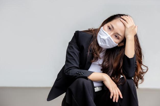 La donna di affari asiatica di tristezza si stanca e si siede sul pavimento come lavoro perso nella crisi del coronavirus che fa la disoccupazione di fallimento sulla parete bianca con la maschera