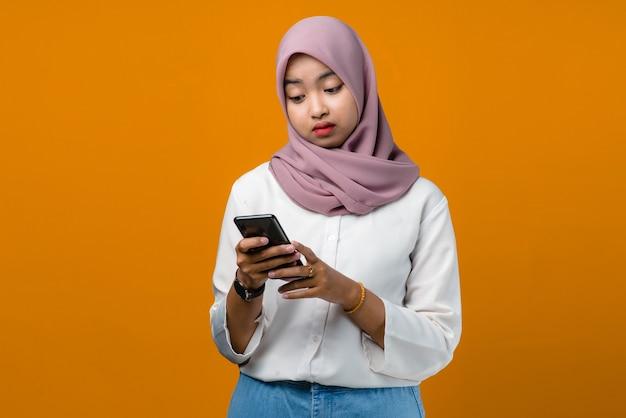 Giovane donna asiatica di tristezza che per mezzo del telefono cellulare su colore giallo