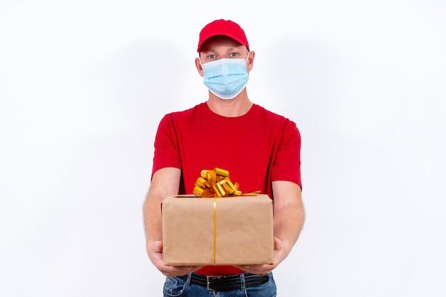 Consegna sicura di regali per le vacanze. un corriere in uniforme rossa e maschera medica protettiva tiene la scatola con un fiocco