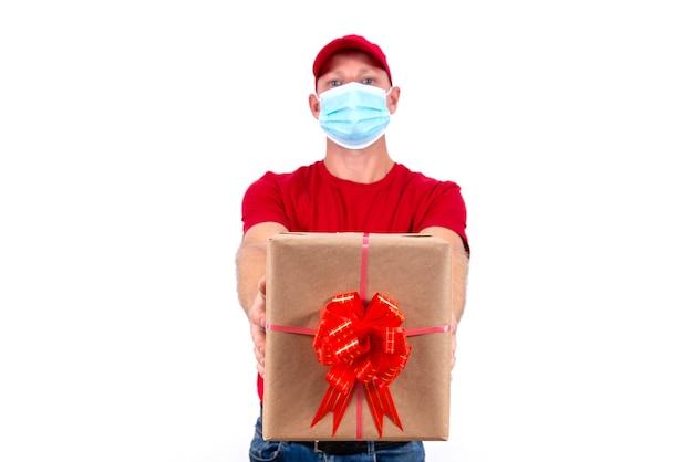 Consegna sicura di regali per le vacanze. un corriere in uniforme rossa e maschera medica protettiva tiene la scatola