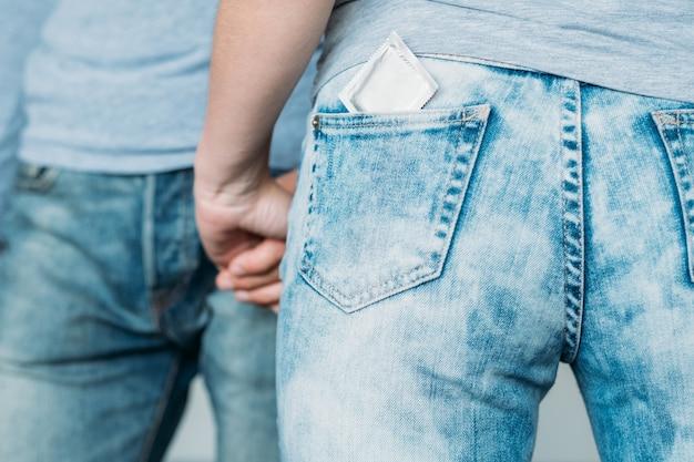 Amore sicuro e concetto di salute. protezione del preservativo da hiv e aids. backview di una donna con un contraccettivo nella tasca dei jeans