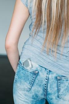 Sesso sicuro. preservativo come prevenzione della gravidanza. backview femminile con un contraccettivo nella tasca dei jeans
