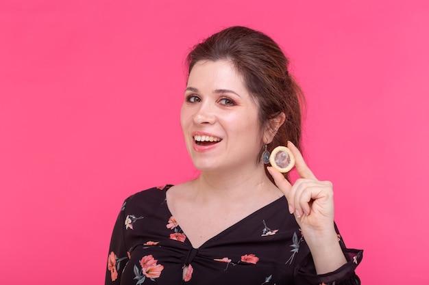 Concetto di sesso sicuro, salute e contraccezione - donna che tiene in mano un preservativo su sfondo rosa