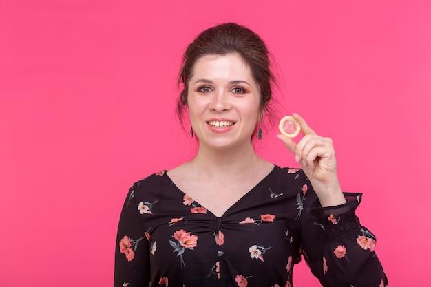 Concetto di sesso sicuro, salute e contraccezione - donna che tiene in mano un preservativo sulla parete rosa