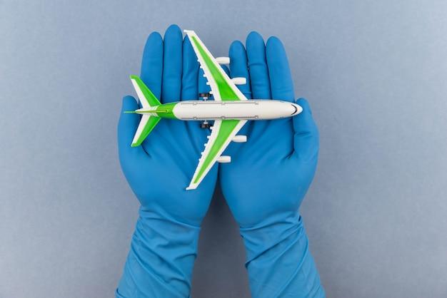 Concetto di viaggi sicuri. aereo nelle mani in guanti medicali. volo in sicurezza e viaggio durante la quarantena e il blocco.