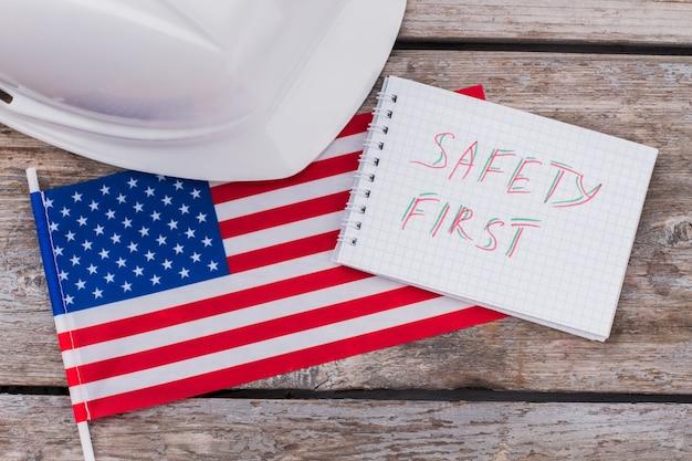 Sicurezza dei lavoratori edili americani. bandiera degli stati uniti e blocco note con casco.