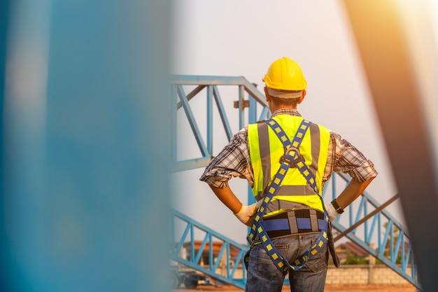 [costruzione di un corpo di sicurezza] ingegnere che lavora in una struttura di tetto in metallo, ingegnere edile indossa uniforme di sicurezza in altezza ispezione dell'attrezzatura di copertura metallica per lavori industriali.