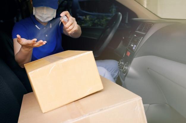 Corriere del servizio di consegna di sicurezza durante la pandemia di coronavirus (covid-19), autista di corriere che indossa una maschera protettiva medica che spruzza spray disinfettante con alcool sulle mani sopra le scatole di cartone nel furgone.