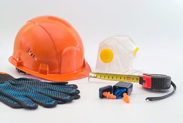 Attrezzatura di sicurezza con casco, respiratore, tappi per le orecchie e guanti isolati su bianco. mezzi di protezione per una grande impresa industriale.