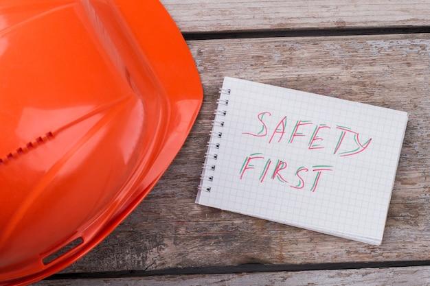 Primo concetto di sicurezza. casco protettivo del costruttore e blocco note sulla superficie del tavolo in legno invecchiato.