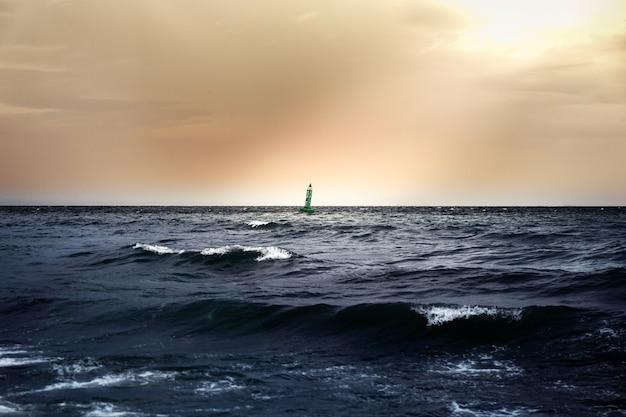 Sicurezza che galleggia sul mare in cielo nuvoloso al tramonto