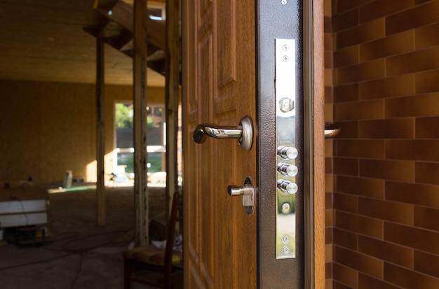 Serratura di sicurezza su una nuova porta d'ingresso in legno che mostra i tre cilindri di sicurezza richiesti dalle compagnie assicurative per le migliori quotazioni di premio