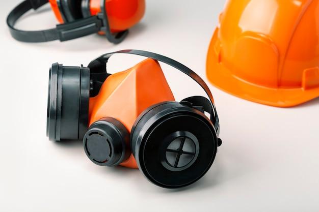 Equipaggiamento protettivo di sicurezza, respiratore, casco e cuffia sulla superficie grigia.