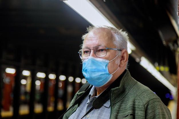 Sicurezza in un luogo pubblico durante l'epidemia di un uomo maturo che indossa una maschera medica usa e getta della metropolitana di new york durante l'epidemia di coronavirus di covid-19.