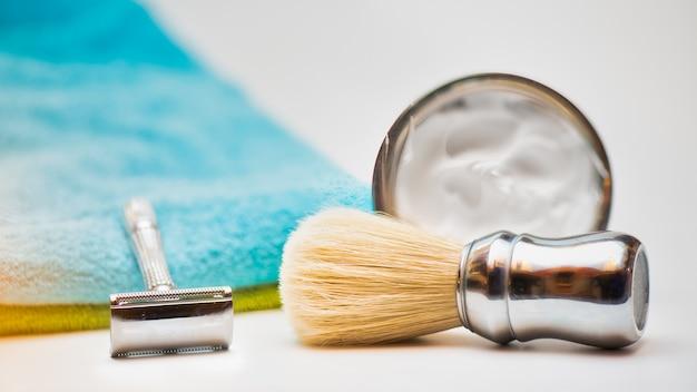 Dettaglio del rasoio di sicurezza con pennello e schiuma da barba