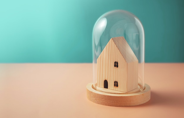 Zona di sicurezza, concetto di assistenza sanitaria. mini casa in legno all'interno di una copertura a cupola in vetro