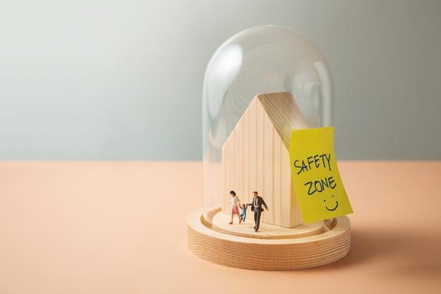 Zona di sicurezza, amore e concetto di cura. figura in miniatura di famiglia che cammina all'interno di una cupola di vetro