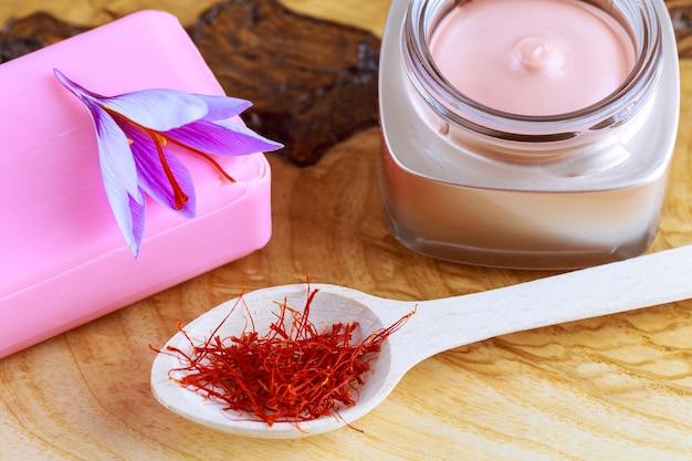Fiore di zafferano su sapone e crema cosmetica su uno sfondo di legno. crema con estratti di zafferano. zafferano secco in cucchiaio di legno.