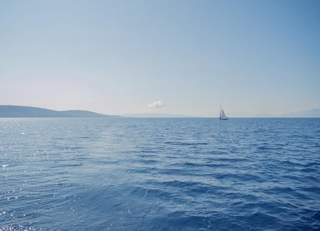 Barca a vela su acque calme sotto un cielo blu chiaro clear