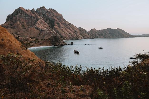 Una barca a vela che galleggia sul mare circondata da colline vicino all'isola di padar labuan bajo