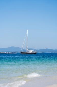 Una barca a vela vicino ad una spiaggia