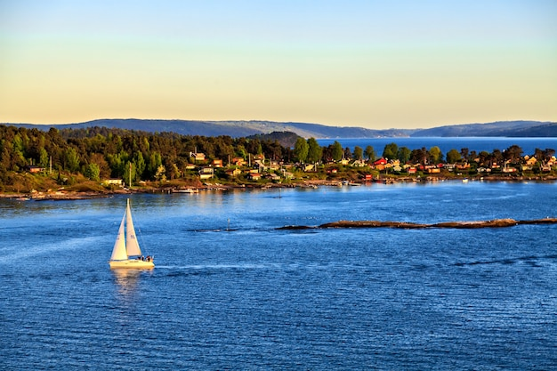 Barca a vela al largo della costa con vista sulla città e sulle montagne