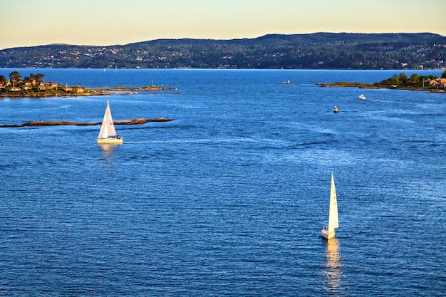 Barca a vela che naviga verso il tramonto in una serata tranquilla