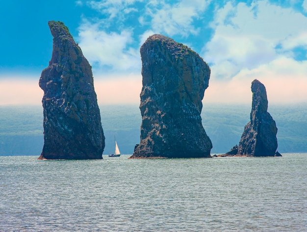 La barca a vela naviga vicino alla costa e alle rocce sulla penisola di kamchatka