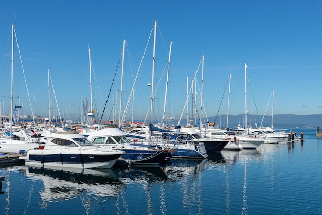 Barche a vela ea motore nel porto marittimo in tempo soleggiato luminoso contro un cielo senza nuvole blu