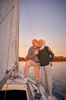 Navigando al tramonto per tutta la lunghezza di una coppia anziana felice che si tiene per mano e si abbraccia mentre sta in piedi sopra